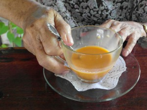 Elderly person holding tea cup